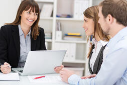 Young couple sitting in an office talking to a woman broker or investment adviser-1