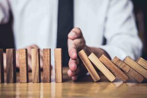 Businessman stopping domino effect on table