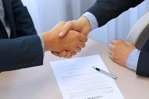 Two People Shaking Hands After Signing a Contract