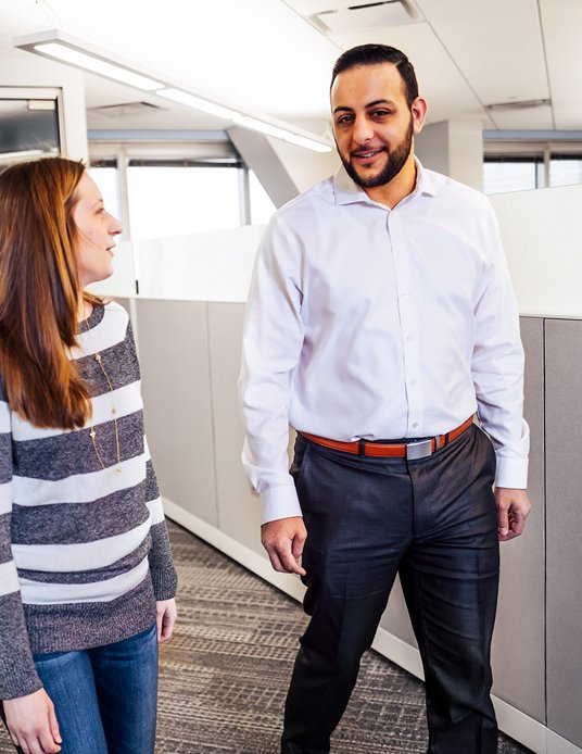 two employees talking and walking through the office