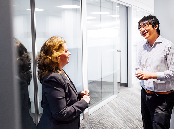 professionals chatting in the office hallway