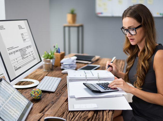woman sitting at desk working with calculator and paper and computer