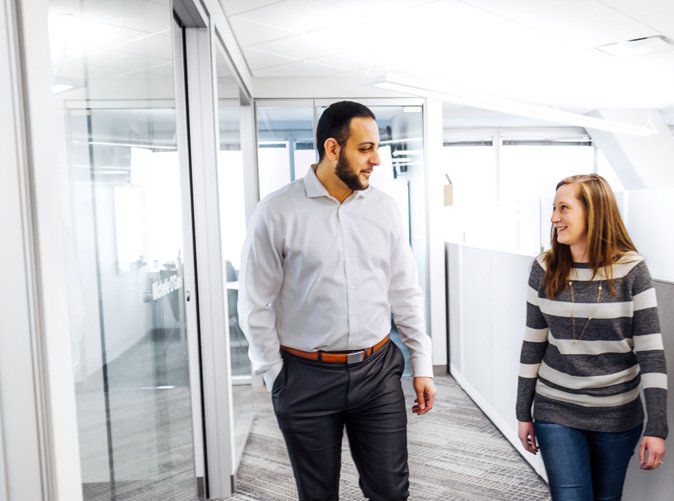 man and woman talking and walking through office