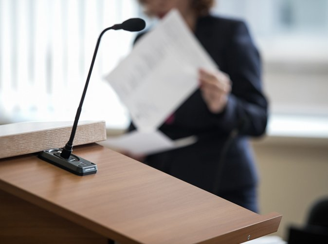 professional standing behind podium with paper