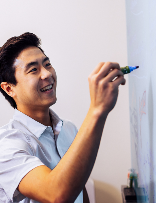 man writing on whiteboard with marker