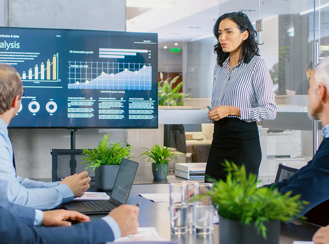 woman presenting data to team in a professional office