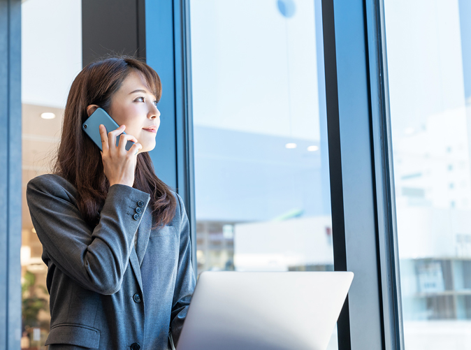 woman using cell phone and looking out a large office window