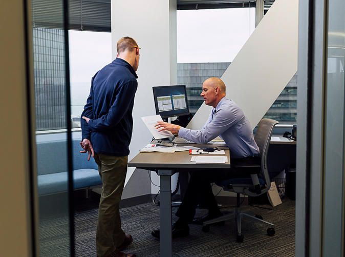 two professional men talking in an office