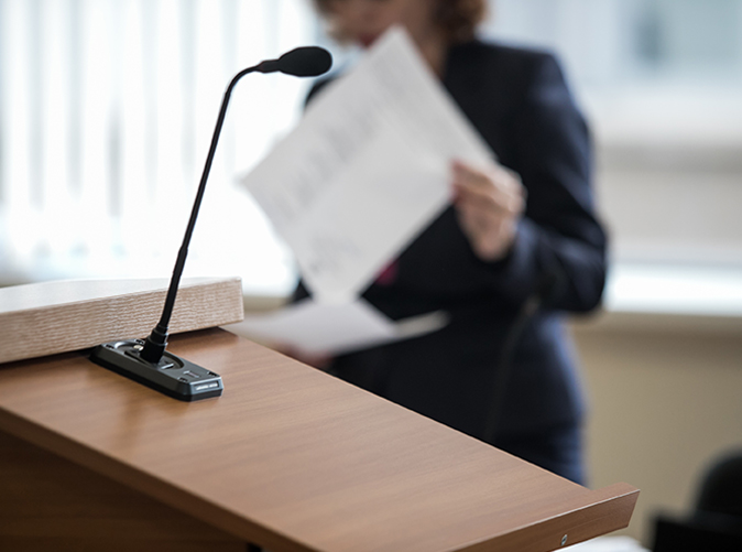 professional standing behind podium and holding paper