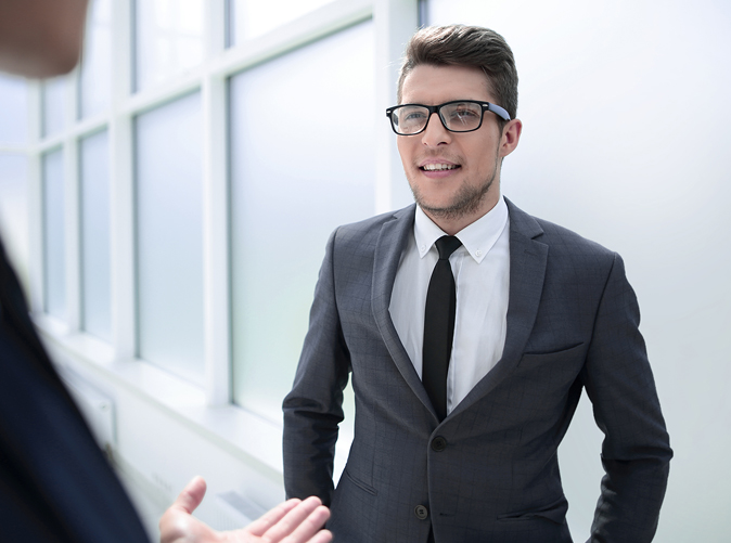 man wearing suit talking with coworker