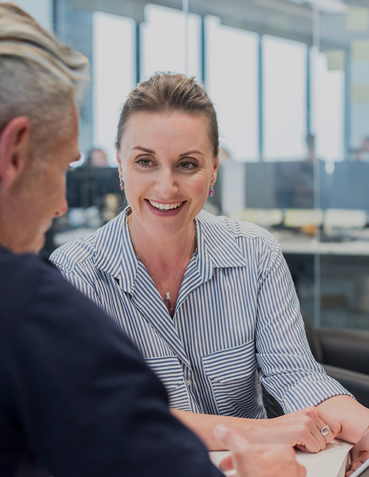 woman smiling talking with colleague