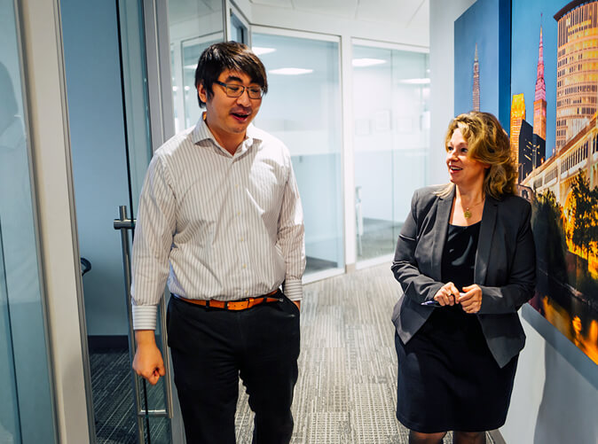 two Meaden and Moore professionals talking in the hallway of an office building